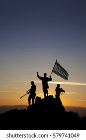 Three armed soldiers with the Israeli flag on the top of the mountain