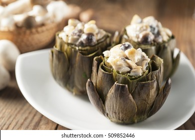 three artichokes filled with mushrooms au gratin on a white plate and wooden background