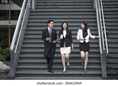 Three Asian  Business people talking while walking down stairs outside.