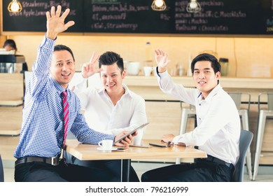 Three Asian businessmen talk about coffee