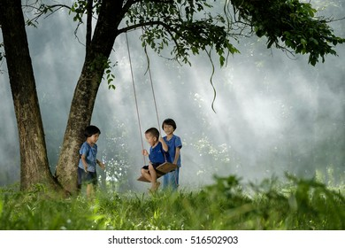 Three asian children playing swing under the tree in leisure time