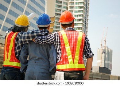 Three asian construction workers looking ahead together, thinking about new project, renovate old buliding. Engineer head of new project, coworker discuss about action plan to work. Strong team.