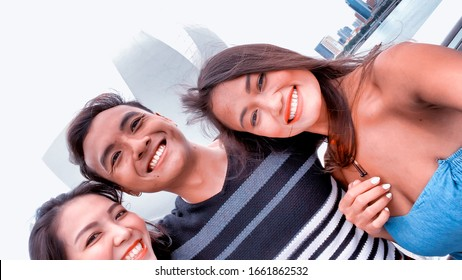 Three asian friends enjoying outdoor city life, taking selfies. Friendship and holiday concept.