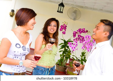 Three Asian friends having chatting and having fun in an outdoor setting.