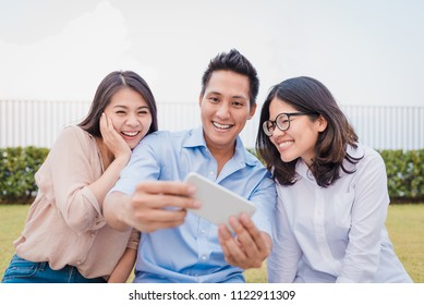 Three Asian friends having fun while watching somethings on smartphone