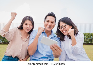 Three Asian friends having fun and celebrate while watching somethings on smartphone