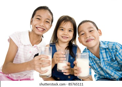 three asian kids with glasses of milk, isolated on white background