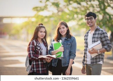 Three Asian peoples portrait, Scholarship Students smile and fun in park at university. Life of studying and friendship concept.