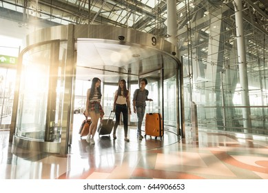 Three asian traveler friends entering airport with happy face