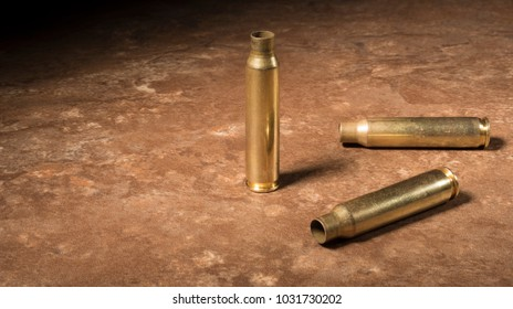 Three assault rifle cartridges that have been shot on sitting on a beige floor