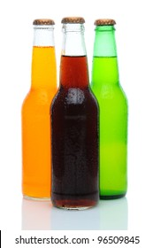 Three Assorted Soda Bottles with condensation . Orange, Cola, and Lemon Lime sodas in a grouping on White