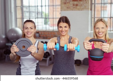 Three athletic fit young women holding up an assortment of different types of weights in a gym as they stand in a line smiling at the camera