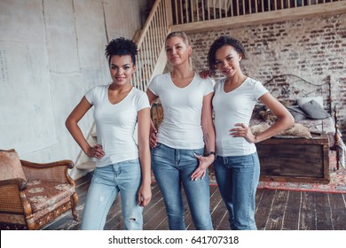 Three attractive girls in white T-shirts are standing at home.