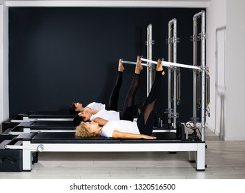 Three attractive and slim women exercise on reformer tower