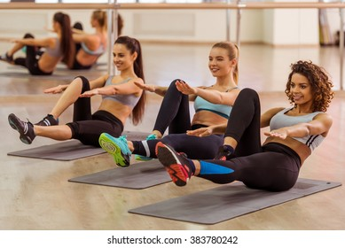Three attractive sport girls smiling while doing abs lying on yoga mat in fitness class