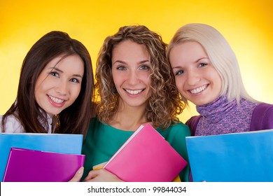 Three attractive students holding exercise books on a yellow background