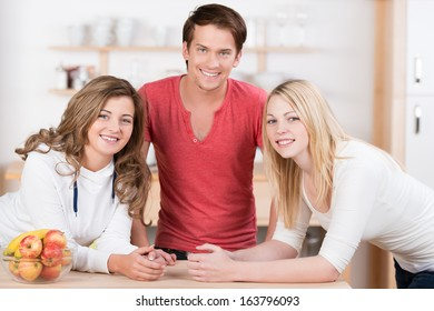 Three attractive young teenage friends relaxing in the kitchen with a handsome young man in the centre with two young women on either side all smiling happily at the camera