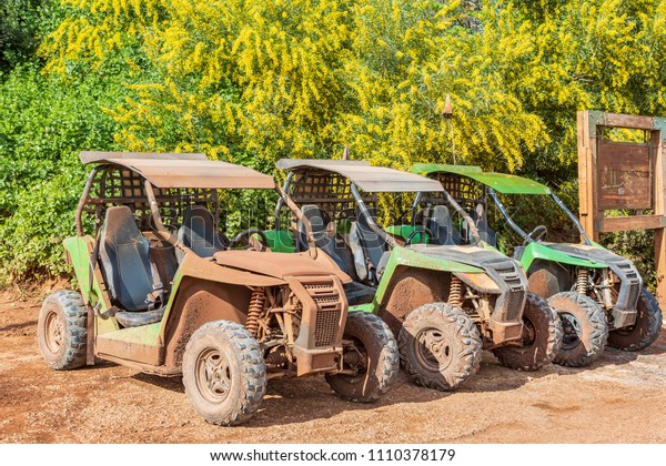 Three ATV spattered with mud after arrival, standing near the bushes of mimosa