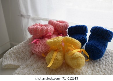 Three baby wool shoes, one pink, one blue and one yellow. They are above a handmade woven white pullover, also for a newborn. They can be use for triplets.