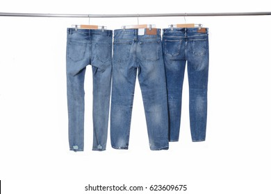 Three back blue jeans on hanger