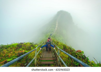 Three backpackers hike the stairway to heaven up into the clouds.