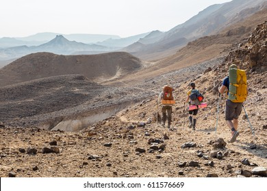 Three backpackers tourists group walking hiking rocks desert path trail marking sign purple trailblazing marker, , Ramon crater valley, Israel tourism traveling.