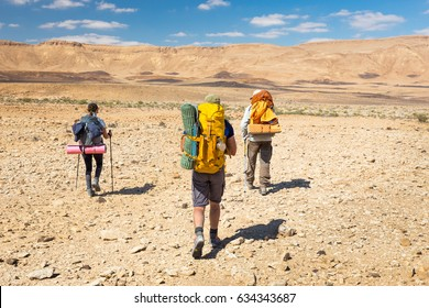 Three backpackers tourists mountaineers group walking hiking rocks desert path trail marking sign purple trailblazing marker, , Ramon crater valley, Israel tourism traveling.