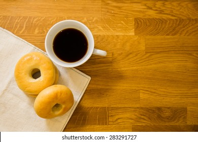 Three bagels and a cub of coffee on the wooden table