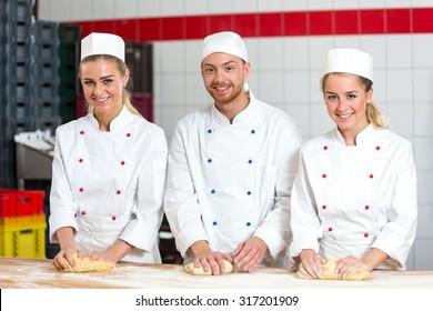 Three bakers in bakery kneading fresh dough