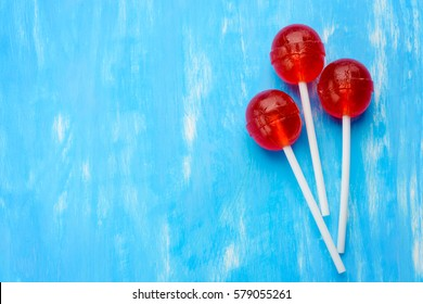 Three ball red lollipops on white sticks. Central lollipop above, at the right edge, on the blue background. Asymmetric ball lollipops minimalism.