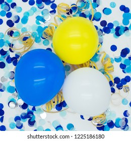 three balloons with blue confetti, yellow streamers on white background