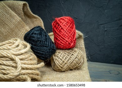 Three balls of natural hemp twine with coarse fibers in a natural brown, red and black on sackcloth fabric over a rustic wood grey background
