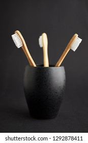 Three bamboo toothbrushes in a black glass on a dark background