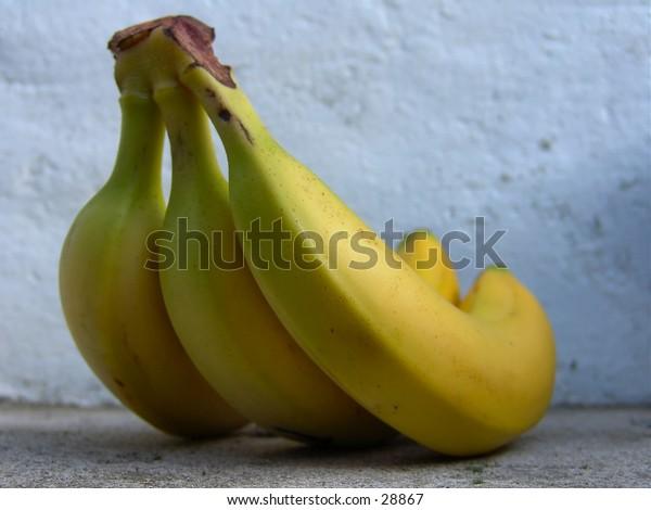 Three bananas by a concrete wall