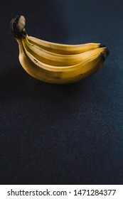 three bananas on dark background shot at shallow depth of field, food ingredients and agricolture concept