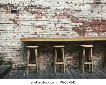 Three bar stools in the backyard of a pub in New York. Grungy brick wall with peeling paint with a sign which says please be courteous to our neighbors. Hip back garden of a bar in the city, no people