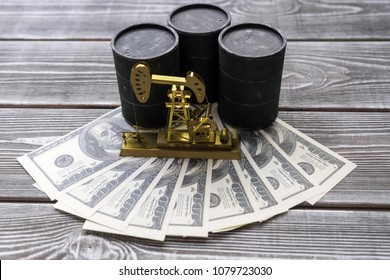 three barrels of oil, neftechka, American dollars against the background of a wooden table. production, sale of petroleum products.