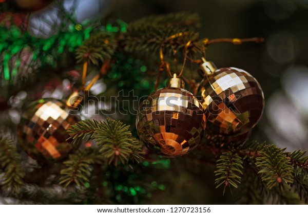 Three baubles hanging on the Christmas Tree in the Northern Finland. These ornaments are not so traditional. They look almost like disco balls.