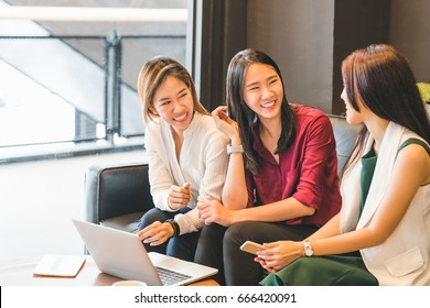 Three beautiful Asian girls chatting on sofa at cafe or coffee shop together. Gossip talks, Casual lifestyle with gadget technology, startup SME, college students or working business woman concept