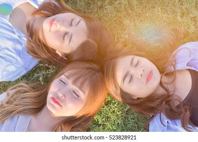 Three beautiful asian girls are laying on the sunny glade with smail and close eyes.Dress in casual and jeans.