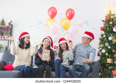Three beautiful asian girls and a man celebrating Christmas or the New Year's Eve party