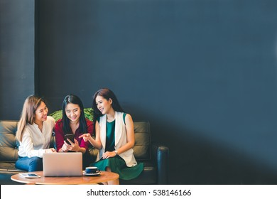 Three beautiful Asian girls using smartphone and laptop, chatting on sofa together at cafe with copy space, modern lifestyle with gadget technology or working woman on casual business concept
