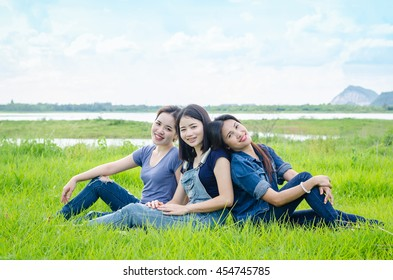 Three beautiful asian women sitting in meadow and smile