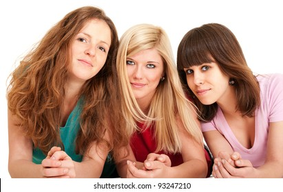 Three beautiful brunette, blonde and redhead girls lying down isolated on white