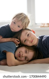 Three beautiful children, boy brothers, having family portrait, hugging, lying in bed
