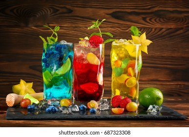 Three beautiful and delicious mojitos with blueberries, strawberries, and grapes. Colorful alcoholic drinks on a wooden background. Blue mojito with mint. Red and yellow mojito with ice and carambola.