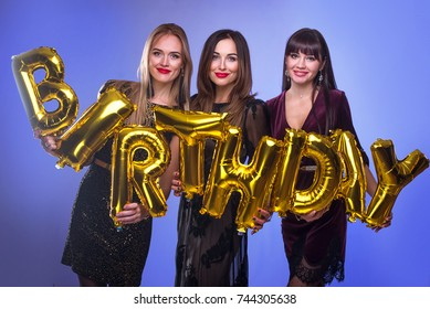 Three beautiful elegant women celebrate birthday and holding balloons in the form of inscription birthay. People celebrate the holiday