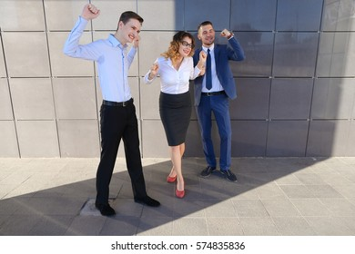 Three beautiful energetic contemporary people, young entrepreneurs, students laugh, rejoice success, smiling and posing for camera near business center. One of guys dressed in blue classic suit, white