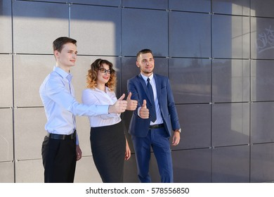 Three beautiful energetic young people, two boys and girl showing thumbs up, laughing, smiling and posing for camera near business center. One of guys dressed in blue classic suit, white shirt with
