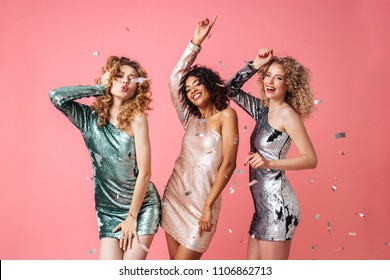 Three beautiful excited women in shiny dresses dancing under confetti rain isolated over pink background